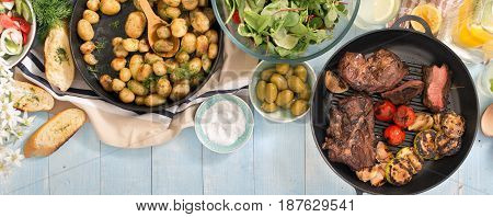 Grilled steak grilled vegetables potatoes salad different snacks and homemade lemonade on a blue rustic wooden table top view