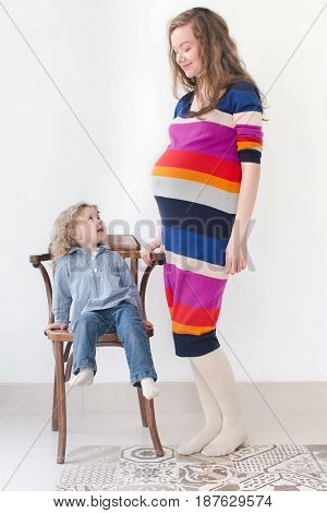 A young pregnant woman 30 years old stand and looks at her daughter sitting on a chair in studio on white background, contemplating, speaking, smiling, communicate, listen each other