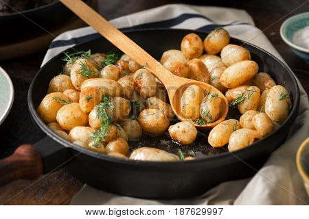 Fried young potatoes in a cast-iron frying pan close up