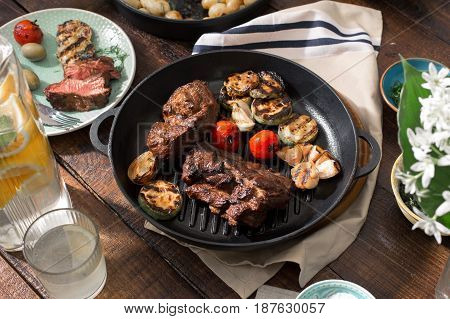 Dinner table concept. Beef steak grilled in a cast-iron grill pan with grilled vegetables on wooden table