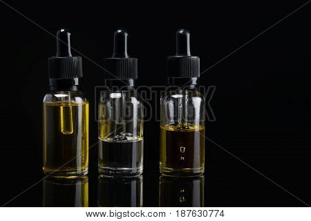 three liquid bottles for e cigarette on black background