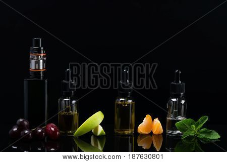 Fruit flavors in bottles for an electronic cigarette on a black background