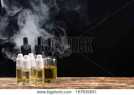 Bottles with fragrant liquids for an electronic cigarette on a black background with the right