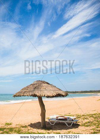 A straw umbrella and deckchair on kahandamodara beach just outside of Tangalle Sri Lanka.