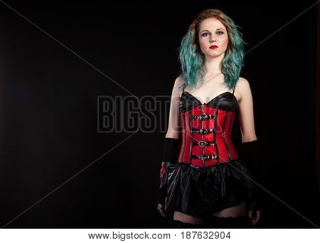 Fashion woman in fetish red leather corset on black background in studio photo. BDSM and dominatrix