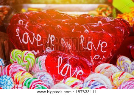 Heart shaped lollipop with word love on street market type of hard candy confectionery