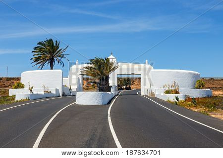 Road With White Entry Gate And Palm Trees, Lanzarote Spain