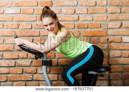 Active Woman Using Exercise Bike At The Gym.