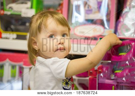 Happy little girl chooses toys in a children's store, telephoto