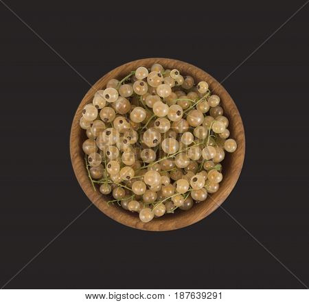 White currants in a wooden bowl. Top view. Ripe and tasty currants isolated on black background.