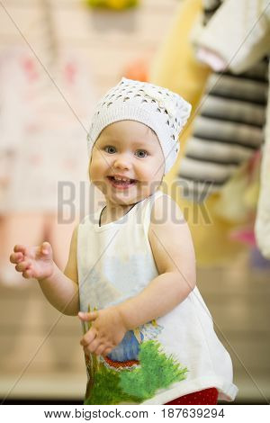 The little baby girl dancing in clothes store for children