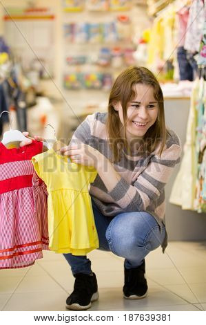 Mother shows dresses for her daughter - little girl in children clothes store, telephoto