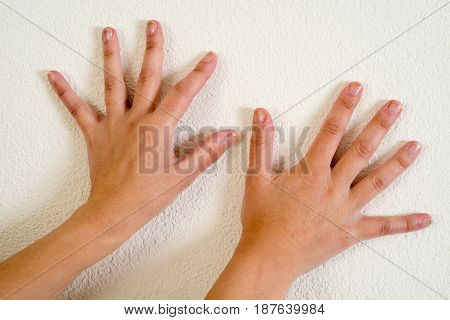Two woman hands on a white wall