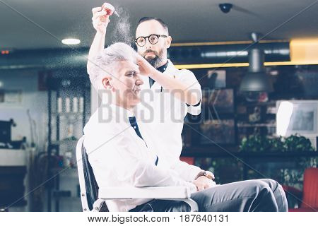 Side view of barber applying powder on a head of mature man.