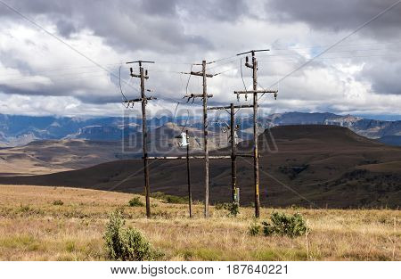 Poles And Overhead Powerlines Against Mountain Landscape