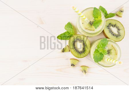 Decorative frame of green kiwi fruit smoothie in glass jars with straw mint leaf cute ripe berry top view. White wooden board background copy space.