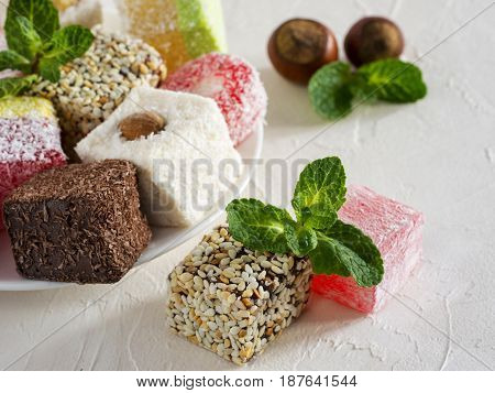 Turkish delight on white rustic background. Turkish deligh set. Assorted traditional turkish delight on oriental background