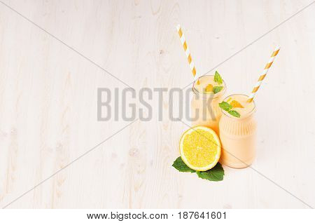 Freshly blended orange citrus smoothie in glass jars with straw mint leaf copy space. White wooden board background.