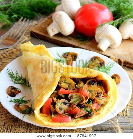Stuffed omelette on a plate. Homemade omelette with mushrooms slices, tomatoes and dill on a plate, ingredients, fork on a vintage wooden table. Easy and delicious vegetarian breakfast. Rustic style