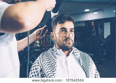 Professional hairdresser drying hair of man in barbershop. Horizontal indoors shot.