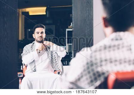 Horizontal indoors shot of man in chair looking at mirror in barbershop.