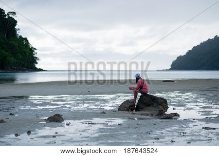 Woman Sitting On Rock Among Moist Sand Beach. Front Of Her Have Blue Sea,sky And Green Forest On Mou