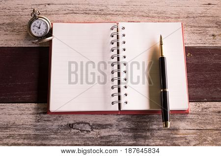 top view and warm tone. pen putting empty notebook red cover and have retro pocket watch putting beside it. old wooden are background. this image for retrobusinesseducation and miscellaneous concept
