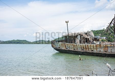 Abandoned Ship Aground On Coast And Have Sea Cloudy Sky, Sea, Mountain Are Background. This Image Fo