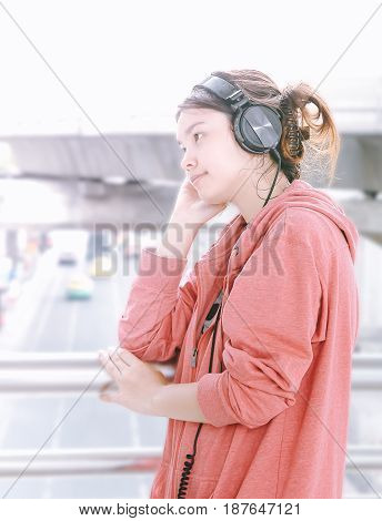 Cute pretty and beautiful girl with soft focus enjoy music with her headphone in the city with copy space