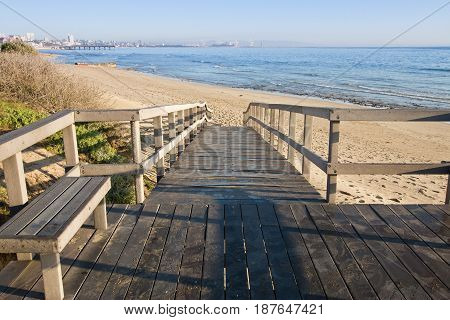 Wooden walkway onto a beach at sunrise with a city in the background