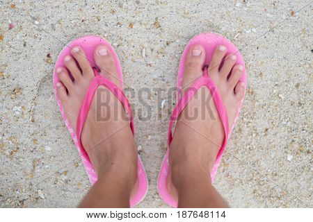 Foot Of Woman Wearing Pink Sandal Standing On Sand Beach Are Background. This Image For Nature And B