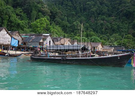 Longtail Boat Parked On Sea Have Old Village And Forest On Mountain Are Background. This Image For L