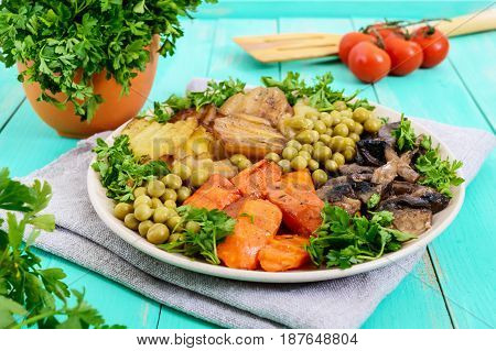 Vegetarian breakfast: baked vegetables (potatoes carrots) mushrooms green peas on a plate on a light wooden background. Healthy food.