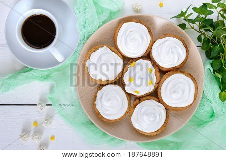 Mini tart with an air cream on a plate and a cup of coffee on a white wooden background. The top view