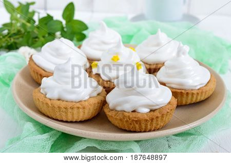Mini tart with an air cream on a plate and a cup of coffee on a white wooden background. Close up