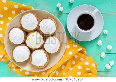 Mini tart with an air cream on a plate and a cup of coffee on a wooden background. The top view
