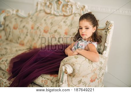 Beautiful girl in a purple dress and flower blouse posing for a photographer.