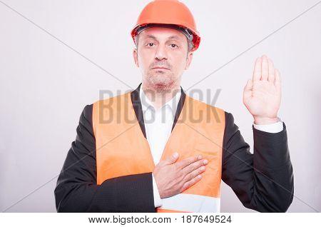 Engineer Wearing Hardhat Making Oath Gesture