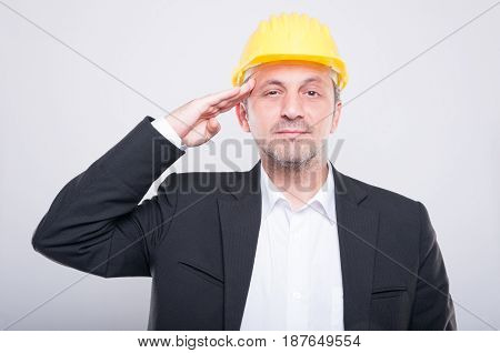 Portrait Of Foreman Holding His Hardhat Making Salute Gesture