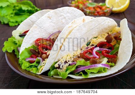 Tacos is a traditional Mexican dish. Tortilla stuffed with chicken bell and hot peppers beans lettuce cheese blue onion with salsa sauce on dark wooden background. Close up