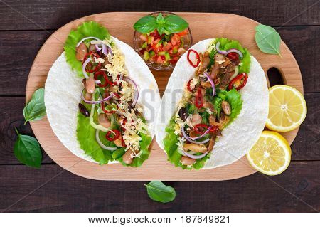 Tacos is a traditional Mexican dish. Tortilla stuffed with chicken bell and hot peppers beans lettuce cheese blue onion with salsa sauce on dark wooden background. Top view.