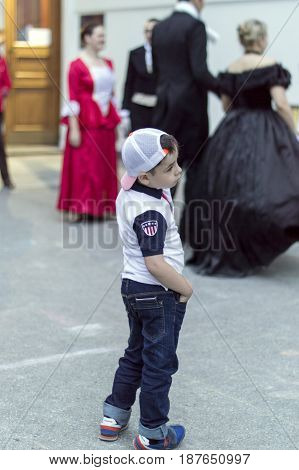 NIZHNY NOVGOROD, RUSSIA  May 20, 2017: Night of museums festival. Little boy in modern clothes standing near Young boys and girl  in the costume of the early 20th century the Russian Museum.