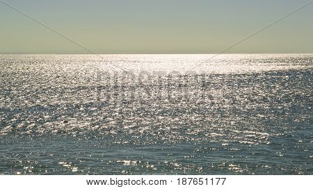 sunlight twinkling and reflecting of the sparkling ocean in high contrast during a hot summers day