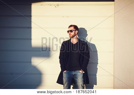 Modern handsome man in glasses posing against wall background