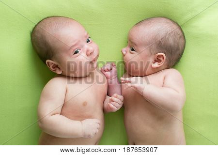 Funny baby infant boys twin brothers lying on green bed