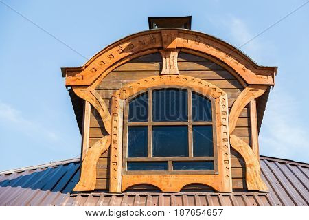 Framed window on the tile roof against the blue sky