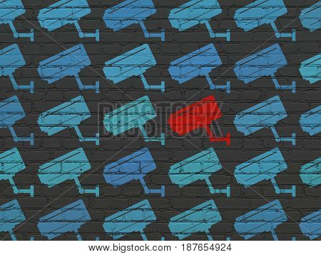 Protection concept: rows of Painted blue cctv camera icons around red cctv camera icon on Black Brick wall background