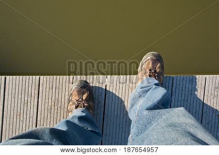Man stepping off a pier into the water with long jeans and shoes