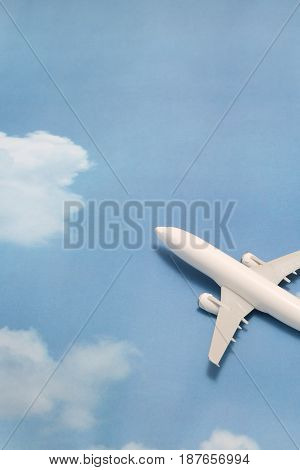 Miniature toy airplane on blue sky with clouds. Trip by airplane. Conceptual image for travel and tourism.