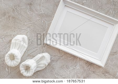 theme for modern baby shower with child shoes and white frame on gray stone background top view space for text
